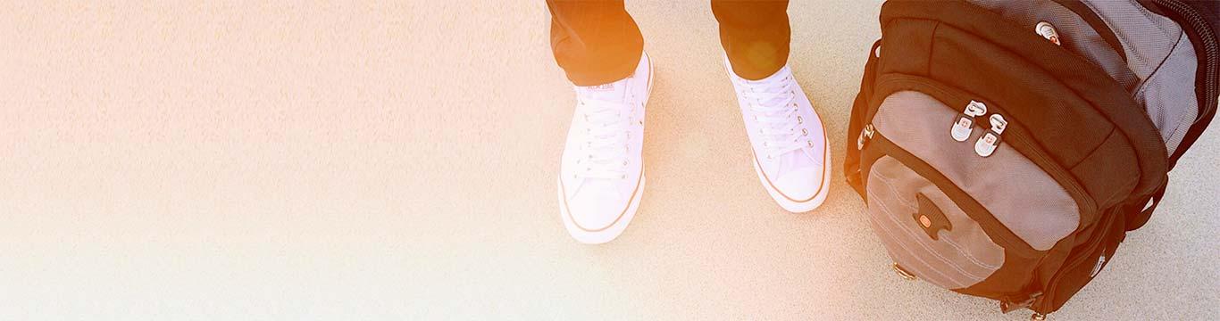 student met witte sneakers en schooltas